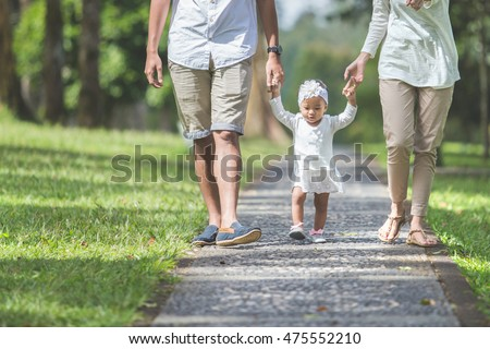 portrait of Beautiful baby learn to walk for the first time with her parents hold her hands