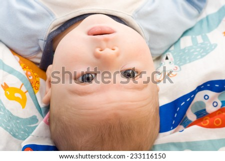 portrait of beautiful baby lying in a crib - stock photo