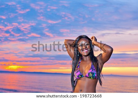 Portrait of beautiful black African American woman posing on the beach at sunset - stock photo