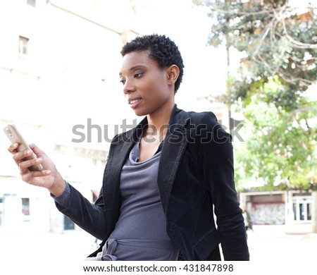 Portrait of beautiful black business woman in financial city, using a smart phone, smiling outdoors. Professional woman using technology, working lifestyle exterior. African american holding mobile. - stock photo