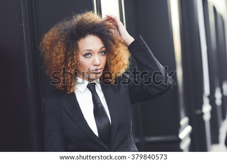Portrait of beautiful black businesswoman wearing suit and tie in urban background. Model of fashion with afro hairstyle.