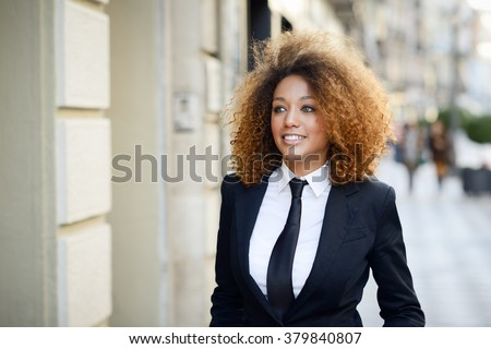 Portrait of beautiful black businesswoman wearing suit and tie smiling in urban background. Woman with afro hairstyle.