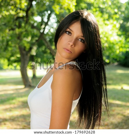 Portrait of beautiful black haired woman in a park