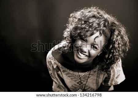 Portrait of beautiful black woman on black background. Studio shot - stock photo