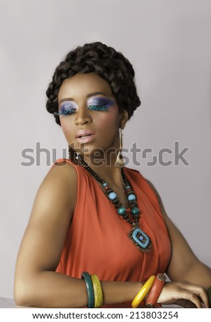 Portrait of beautiful black woman wearing bright orange and turquoise, with creative makeup and false lashes looking down - stock photo