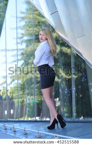 portrait of beautiful blond business woman standing in front of office building in the city - stock photo