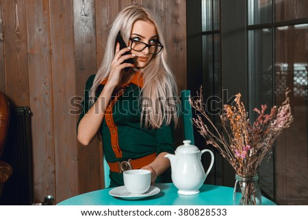 Portrait of beautiful blond business woman talking on the phone and looking away at the window in city cafe. Business concept. Business woman at cafe. Business after hours.