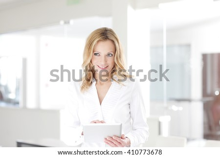 Portrait of beautiful blond businesswoman standing at office and working on digital tablet.