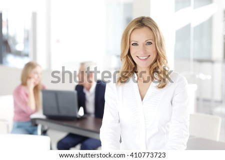 Portrait of beautiful blond businesswoman standing at office while her colleagues working at background.