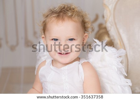 Portrait of beautiful blond curly toddler in a while lace dress with wings as a Cupid in the white room with gold moldings in baroque style near nice chair in baroque style. Saint Valentines Day