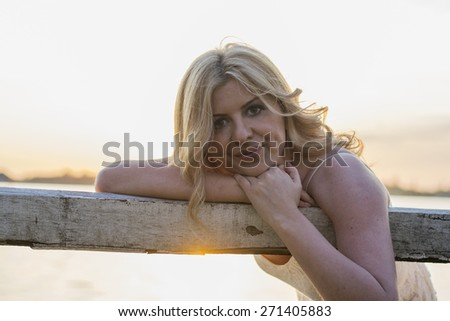Portrait of beautiful blond curly woman sitting on old wooden bench with lake behind.