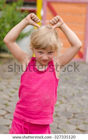 portrait of beautiful blond girl doing funny gestures - stock photo