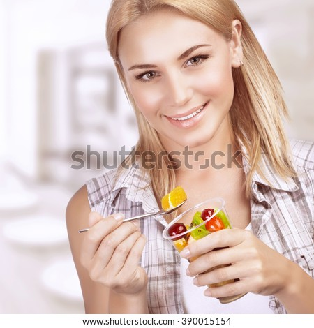 Portrait of beautiful blond girl for breakfast with pleasure eating fruit salad, snaking at home, enjoying healthy nutrition - stock photo