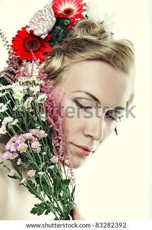 Portrait of beautiful blond girl with flowers in her hair