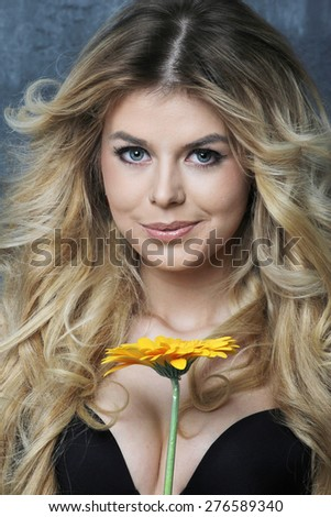 Portrait of beautiful blond girl with red gerbera in black underwear. On blue wall background - stock photo
