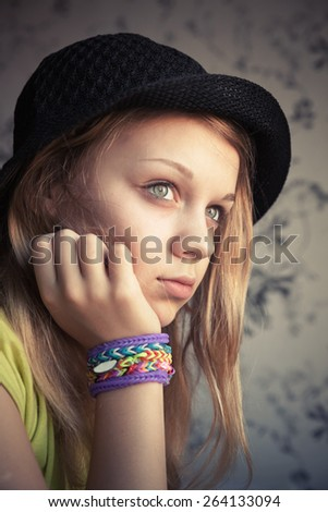 Portrait of beautiful blond teenage girl in black hat and rubber loom bracelets, vintage toned photo, instagram style effect - stock photo