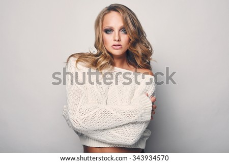 Portrait of beautiful blond woman in white in white sweater - stock photo