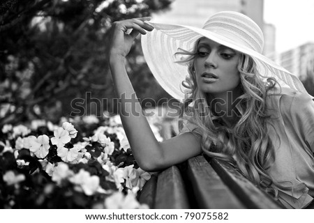 Portrait of beautiful blond woman in white retro hat siting near park flowers. Black-white photo. - stock photo