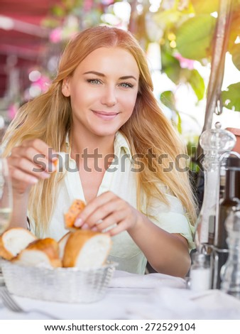 Portrait of beautiful blond woman sitting at outdoors cafe and eating bread, waiting for someone, spending summer vacation in Italy, Europe - stock photo