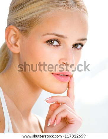 Portrait of beautiful blond woman with finger on lips