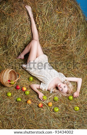 portrait of beautiful blonde country girl posing laying on yellow hay with apples spilled from basket