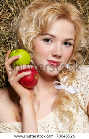 portrait of beautiful blonde country girl sittitng on yellow hay with apples