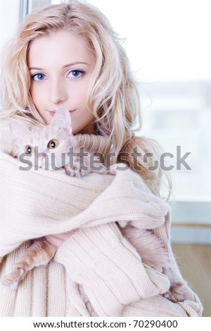 portrait of beautiful blonde girl in pullover with kitten - stock photo