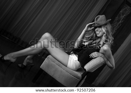 Portrait of beautiful blonde girl wearing hat and sitting in  chair - stock photo