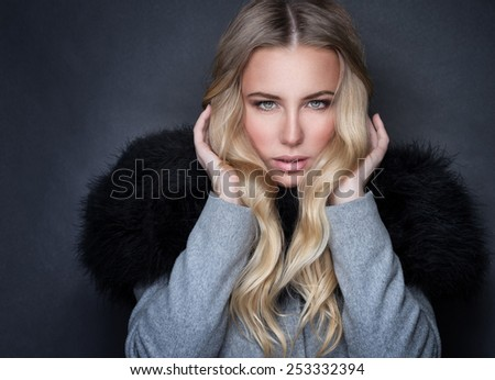 Portrait of beautiful blonde seductive woman on gray background, wearing stylish coat with black fur, sexy look, fashion and beauty lifestyle  - stock photo