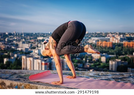 Portrait of beautiful blonde strong woman in sportwear doing workout on the roof of a skyscraper above the big city at early morning. Female sporty muscular body. Dawn and sunrise bright sunny light. - stock photo