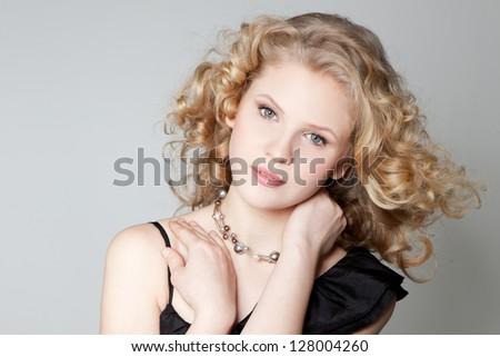 Portrait of beautiful blonde teenage girl in black dress over gray - stock photo