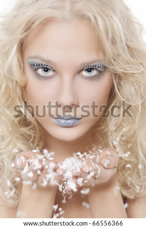 Portrait of beautiful blonde winter snow queen blowing snow flakes from hands - stock photo
