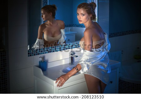 Portrait of beautiful blonde woman in bathroom, posing with mirror. - stock photo