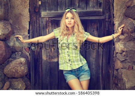 Portrait of Beautiful Blonde Woman on Wooden Door Background. Toned Photo. Modern Youth Lifestyle Concept. - stock photo
