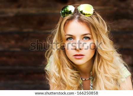 Portrait of Beautiful Blonde Woman on Wooden Wall Background - stock photo