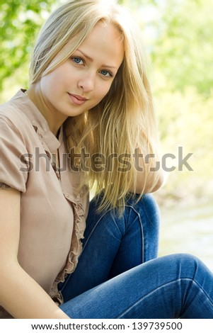 Portrait of beautiful blonde woman outdoors in summer - stock photo