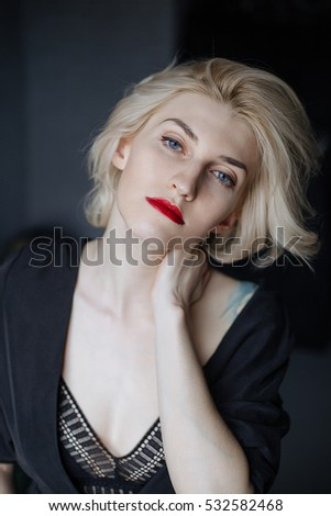 Portrait of  beautiful blonde woman with red lips, blue eyes, short hair, wearing black dress, white clear skin.