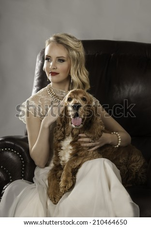 Portrait of beautiful blonde woman with red lipstick and vintage cream dress seated on brown leather couch with pet golden spaniel dog on her lap - stock photo