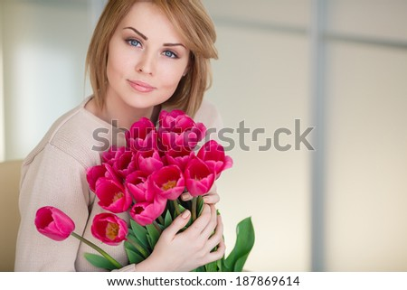 portrait of Beautiful blonde woman with the bouquet of pink tulips in interior background - stock photo