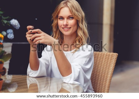 Portrait of beautiful blonde young woman in cafe with phone