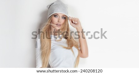 Portrait of beautiful blonde young woman in fashionable cap. Girl looking at camera. - stock photo