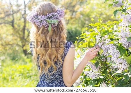 Portrait of beautiful blue-eyed teenager girl with wreath from lilac flowers - stock photo