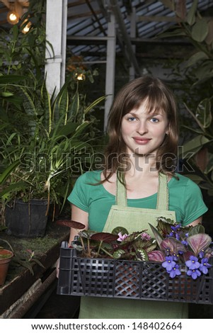 Portrait of beautiful botanist carrying crate full of flower plants at greenhouse - stock photo