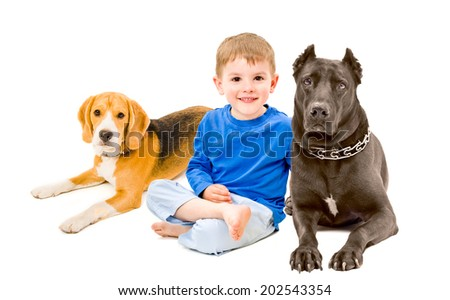 Portrait of beautiful boy sitting with two dogs - stock photo