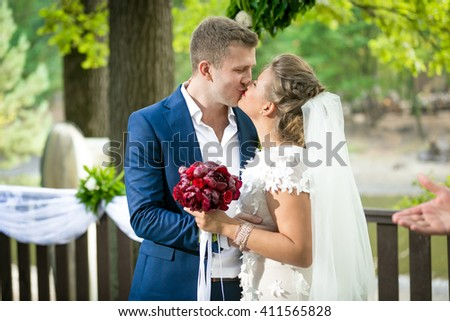 Portrait of beautiful bride and groom having first kiss at park - stock photo
