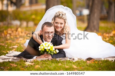 Portrait of beautiful bride and groom lying on grass and smiling at camera