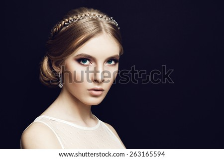 Portrait of beautiful bride at wedding dress in studio, looking at the camera. Newlywed woman. Dark background. Lights makeup and braid hairstyle. - stock photo