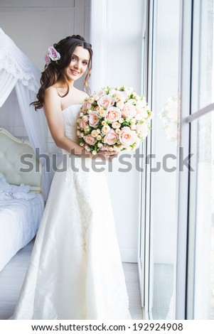 Portrait of beautiful bride model with perfect makeup and hair style in light room in a morning