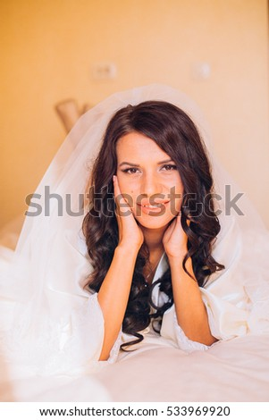 Portrait of beautiful bride. Morning of the bride. Posing on the bed on the wedding morning. Makeup. Brunette girl with long wavy hair.
