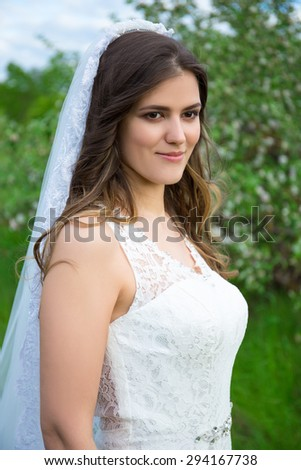 portrait of beautiful bride walking in summer garden